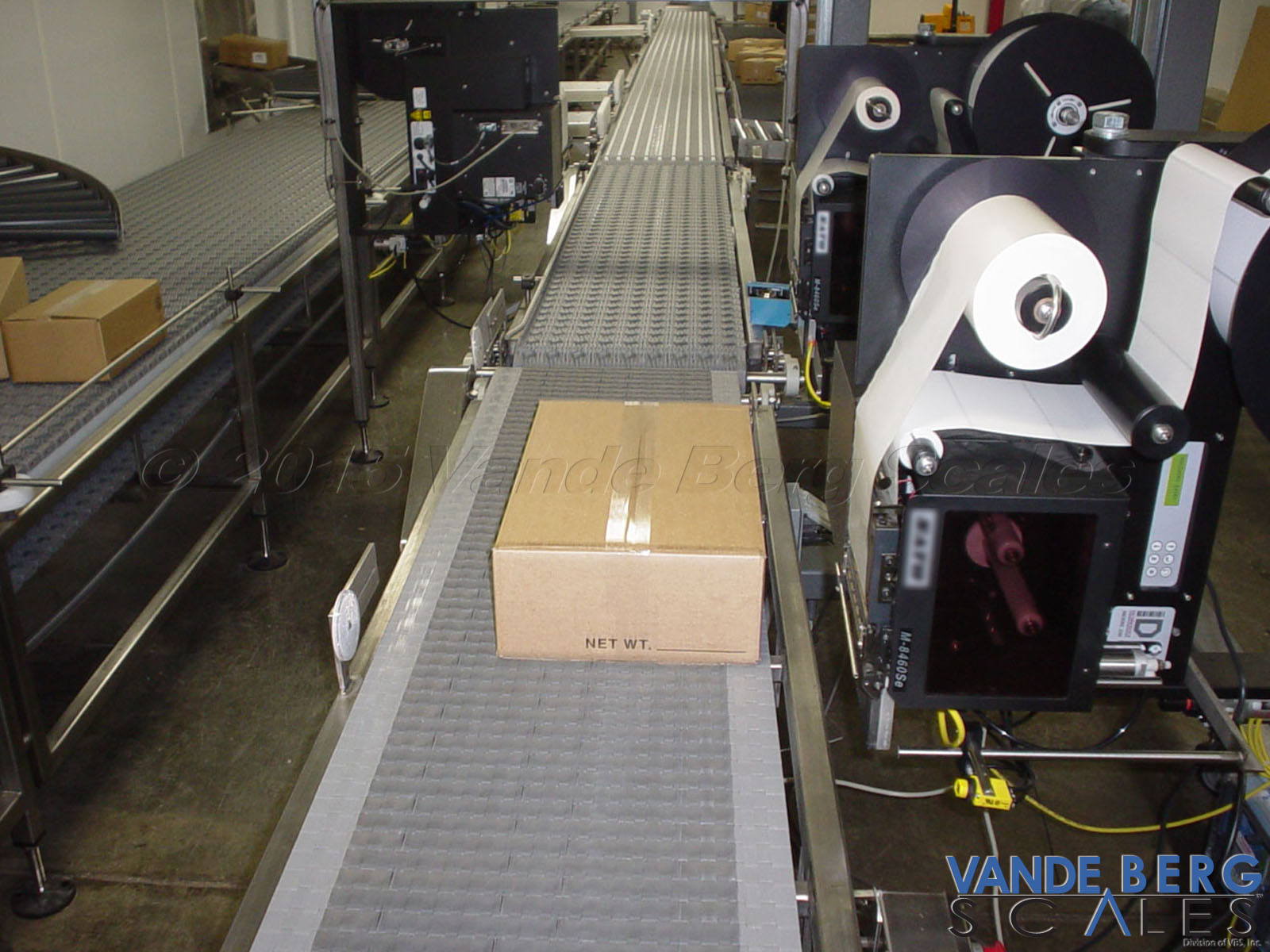 Box conveyor system which weighs and then prints a unique label for each box.  Boxes are aligned against a common edge for label application.