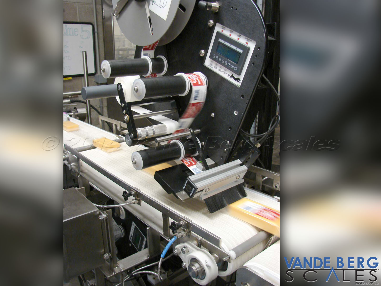 Top and Bottom Cheese Labeling System - unit applies the label at the same speed as the conveyor belt to ensure a wrinkle-free application
