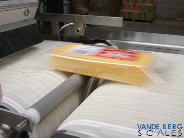 Close-Up of label being applied to cheese package - label is wrapped around a SS flange.