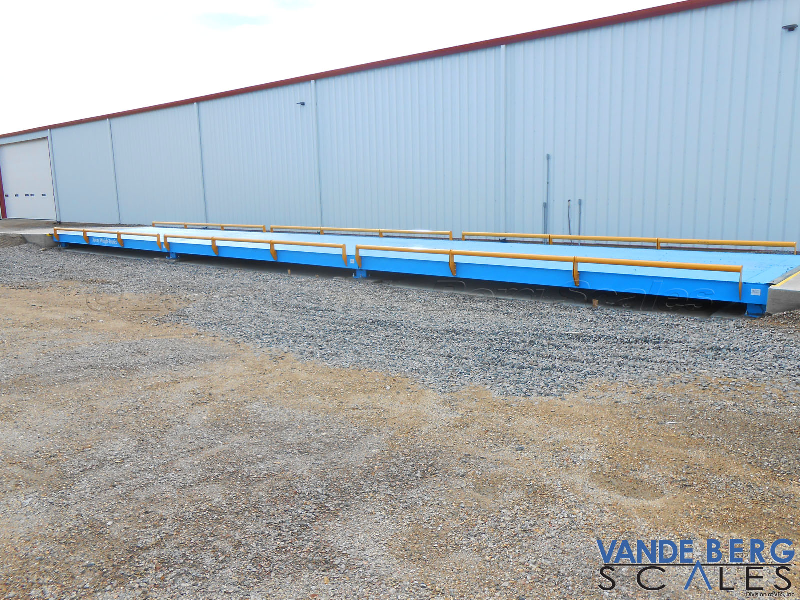 Pitless truck scale next to a warehouse. The convenience of the scale ensures the operator does not exceed road weight limits.